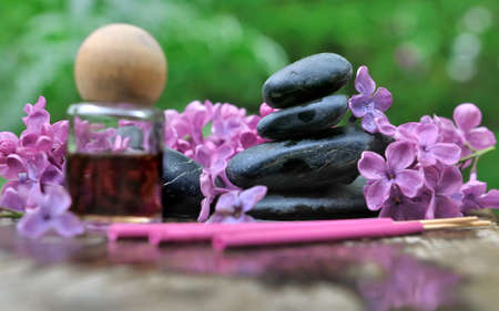 lilacs: incense and essential oil with lilacs and pebbles on green background Stock Photo