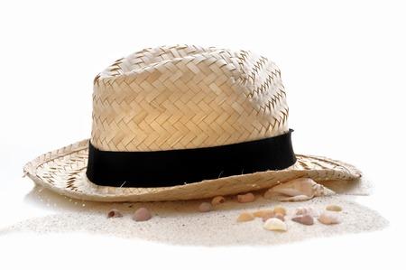sombrero de paja en la arena en el fondo blanco