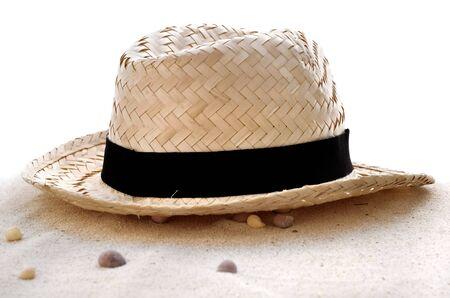 chapeau de paille: chapeau de paille dans le sable sur fond blanc