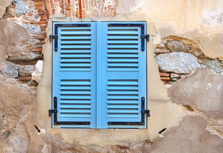 decrepit: little window with blue shutters on a decrepit wall Stock Photo