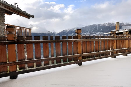 cottage fence: wooden  railing of a terrace with snow -  cottage in Savoie - France
