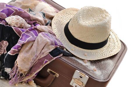 boater: straw hat on a suitcase with sarong isolated on white background