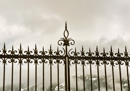 metal gate: black metal gate under gray cloudy sky