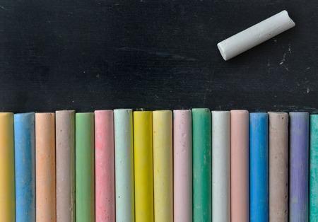 chalks: colorful chalks under  a white chalk on a black board