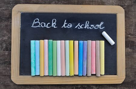 chalks: chalkboard with message Back to school with chalks on wooden background