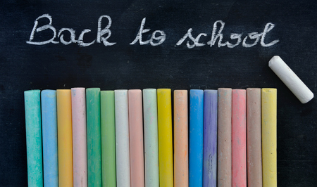 chalks: chalkboard with message Back to school with chalks on black  background