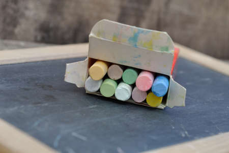 chalks: chalks in a box on a slate on wooden background