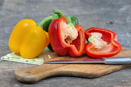red pepper cut in half with others on board with knife