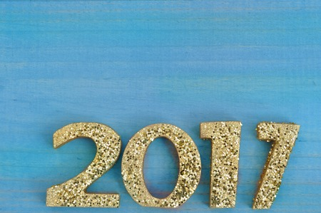 pannel: 2017 with golden figureson blue wooden pannel background Stock Photo