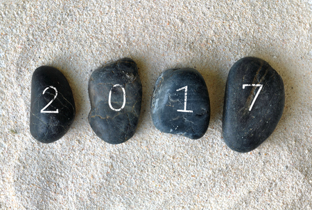 black pebbles: year 2017 writted on black pebbles on sand background