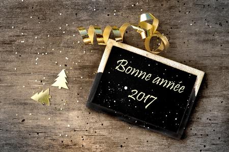 Kleines Schild mit der Meldung guten Rutsch ins neue Jahr 2017 auf französisch auf Holzuntergrund auf einem Schild geschrieben Standard-Bild - 63956844