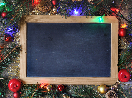 bordering: Christmas ornament bordering a slate  on wooden background