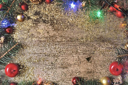 bordering: Christmas ornament bordering a wooden plank with empty space in th middle Stock Photo