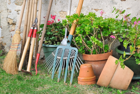 gardening tools along a wall in a garden with flower pots