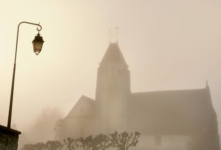 lugubrious: church of a village and a lamppost in the fog