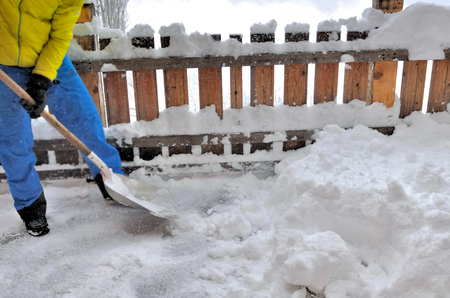 man shoveling the snow on a terrace Stock Photo