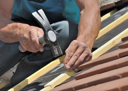 close on hand of a roofer nailing slats on a roof for renovation Stock Photo