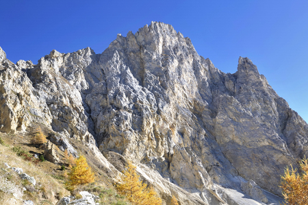rocky wall of a peak mountain under blue sky