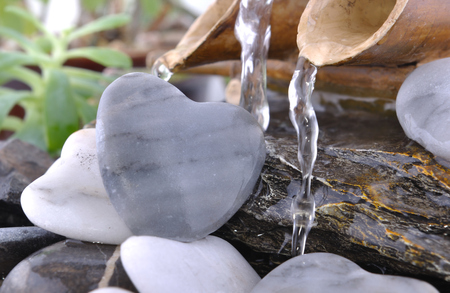 water flowing from little bamboo fountain on heart-shaped pebbles Stock Photo