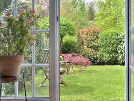 Tuin gezien door de binnenkant van een huis door een deur maakt ramen open