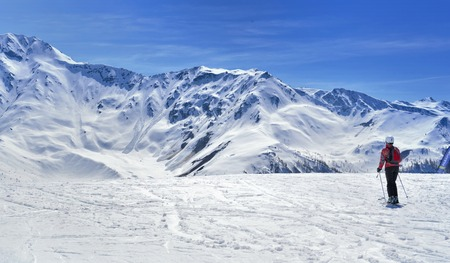 skier on a slope in alpine snowy mountain under blue sky