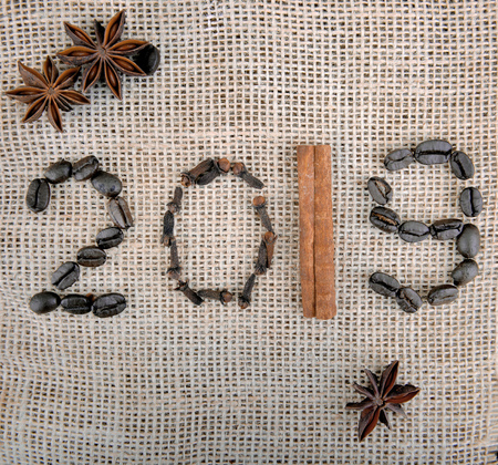 2019 year written with spices and beans coffee on fabric textured background 免版税图像