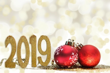 2019 figures next to ed christmas balls and gold glitter onblur lights background Stock Photo