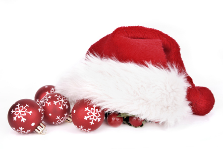 santa klaus cap on red christmas baubles isolated on white background