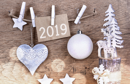 2019 on paper sign and christmas decoration janging to a string on wooden background