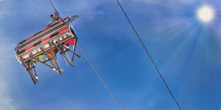 Leute im Skilift von unten gesehen unter sonnigem blauem Himmel