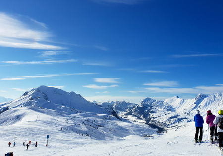 skiers on ski slopes in french alps under blue sky