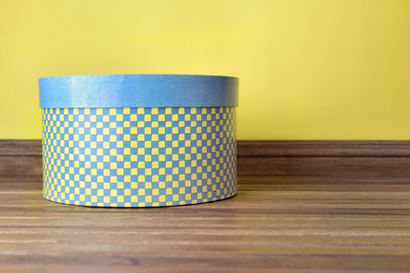 decorative hat box blue and yellow on a wooden floor indoor Standard-Bild - 118228837