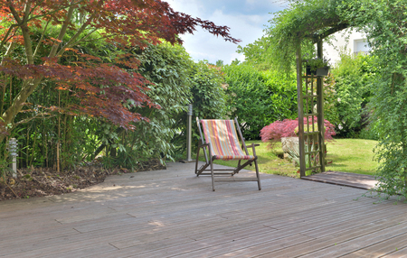 deck chair on a wooden terrace in a landscaped garden