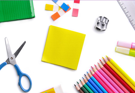 top view on colorful school supplies on white background