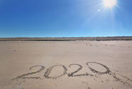 2020 written on the sand under a beautiful sunny blue sky Stock Photo