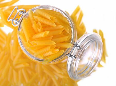 top view on gluten free pasta in a jar open and pasta spilled on white background