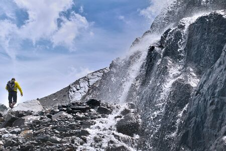 water flowing rocky mountain with an hiker climbing background Фото со стока