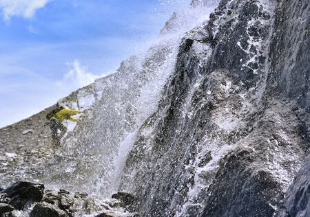 close on water flowing on rocky mountain with an hiker climbing background Фото со стока