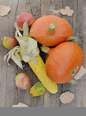 pumpkins corn and red apples on a rustic table with autumnal leaf