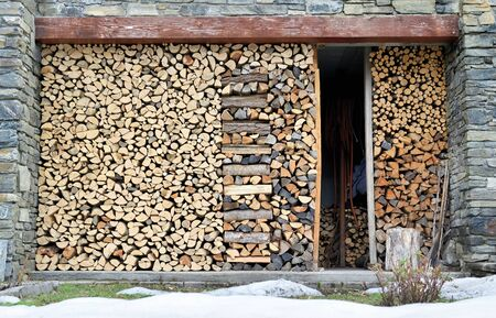 organized pile of firewood forming a wall stored outdoor from a stone cottage