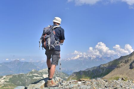hiker standing on the summit of alpine mountain in a summer