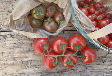 top view on fresh  tomatoes in  a little basket on a wooden rustic background Фото со стока