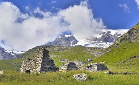 scenic landscape of mountain with ruins in a meadow  and glacier background