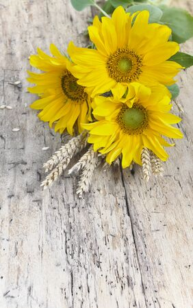 bouquet of sunflowers with dry wheat on a rustic table