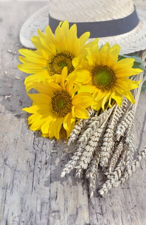 bouquet of sunflowers with dry wheat and a hat background on a rustic table Фото со стока