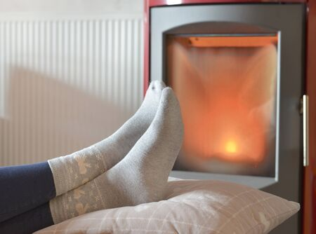 view on the feet of a woman in socks relaxing in front of the heat of a wood stove