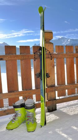 touring ski and shoes against a wooden fence of a snowy terrace with view on mountain Фото со стока