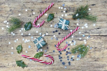 top view on candy canes and christmas decoration in star shaped confetti on rustic wooden background