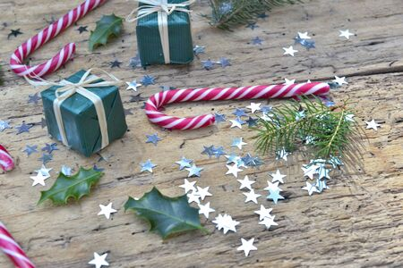 candy canes and christmas decoration in star shaped confetti on rustic
