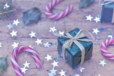 close on a gift in christmas decoration with   candy canes and  star shaped confetti on rustic